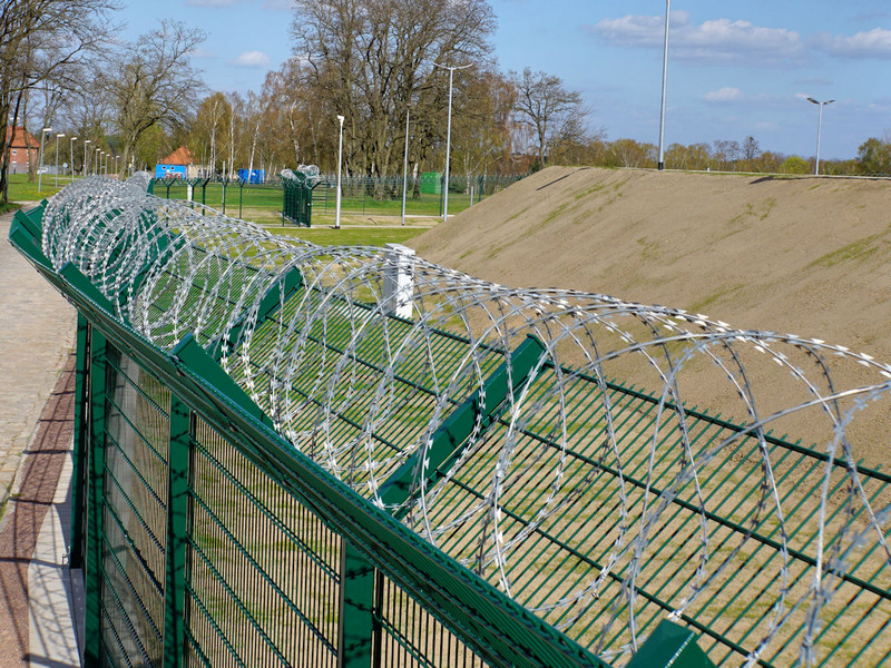 INOVA security fence with extension arms and coiled razor wire